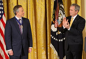 English: President George W. Bush applauds for...