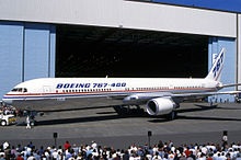 Side quarter view of twin-engine jetliner in front of hangar, with surrounding crowds
