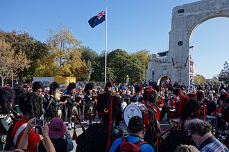 European New Zealanders - The New Zealand flag is raised in the Bridge of Remembrance during an Anzac Day parade in Christchurch, New Zealand.