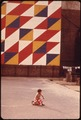 CHILDREN PLAY BENEATH EYE-CATCHING MURAL IN A SMALL CITY PARK ON THE CORNER OF 29TH STREET AND SECOND AVENUE IN... - NARA - 551727.tif