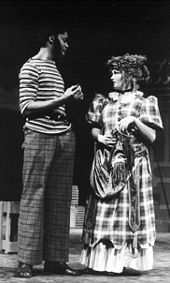 black man with sideburns, striped shirt, and plaid pants talks to white girl in calico dress with hat and purse on a stage