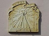Carpe diem est inscrit sur un cadran solaire surmonté d'un soleil.