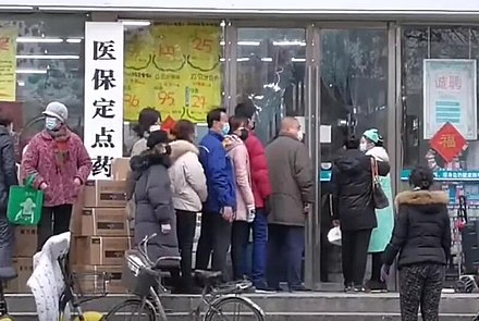 People in Wuhan lining up in front of a drug store to buy surgical masks Citizens of Wuhan lining up outside of a drug store to buy masks during the Wuhan coronavirus outbreak.jpg