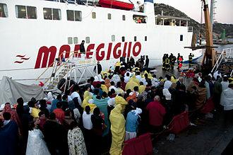 Costa Concordia disaster - Rescued passengers huddle ashore.