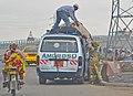 Convoyeur en train de faire descendre un sac d'une automobile.jpg