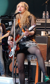 Woman playing guitar, with her left leg up on a monitor.
