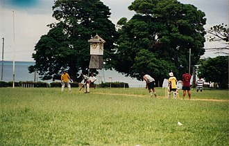 Palm Island, Queensland - Locals playing cricket with the bell tower in the background (1996)