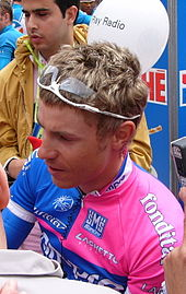 A man signing autographs while wearing a pink and blue cycling jersey.