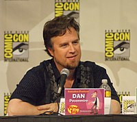 A Caucasian man in his forties, seated at a conference, with a microphone in front of him. He has a pleasant square face, deep-set eyes, dark hair and a brown beard with clean-shaved cheeks and upper-lip. He is casually dressed, relaxed and smiling. Square signs are posted on the wall behind him, bearing the name COMIC-CON in big bright yellow letters around a drawn eye and eyebrow.