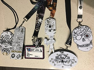DEF CON - Multiple DefCon badges, electronic and non-electronic, and other con badges.