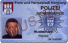 A identity card with a picture, the coat of arms of Hamburg, the police star of Hamburg and the German word sample written across.