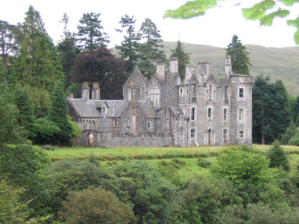Dunans Castle - A granite structure with high walls surrounded by trees and grass