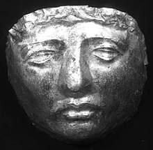 Black and white photograph of a gold death mask resembling a human face