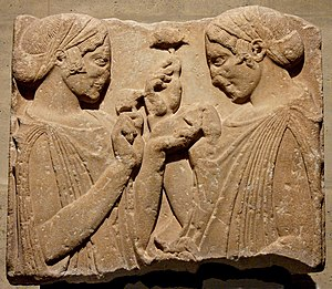 "Peplos - So-called ""Exaltation de la Fleur"" (exaltation of the flower), fragment from a grave stele: two women wearing a peplos and kekryphalos (hairnet), hold poppy or pomegranate flowers, and maybe a small bag of seeds. Parian marble, c. 470–460 BC. From Pharsalos, Thessaly."