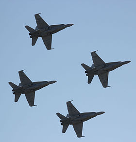 Underside view of four twin-engined military jets in diamond formation