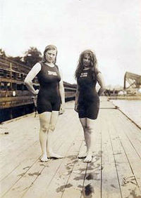Two women stand side by side on wooden decks on a dockside, with one arm on their hips, wearing swimsuits covering their torso and thighs. They both have dark hair longer than their shoulders.