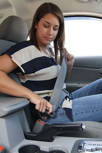 Seat belt - A woman buckling a three-point seat belt