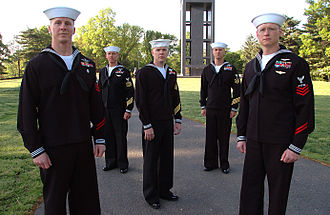 Personnel of the United States Navy - Petty Officers wearing service dress uniforms pose for a photograph in front of the Netherlands Carillon at Arlington National Cemetery.