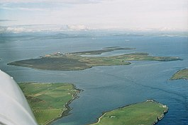 An aerial view of Flotta from the south-west. The oil refinery is visible to the centre-left, with the airstrip further to the left. South Walls is at the bottom and bottom left, and Switha at the extreme right.