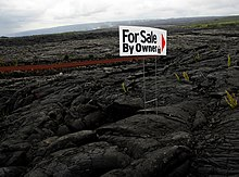 For Sale sign in town site that was destroyed by lava, with active lava flow in background