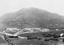 A panoramic view of a military camp at the base of a mountain