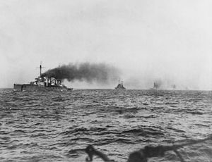 A line of large warships. Thick black smoke pours from their funnels as they steam through choppy seas.