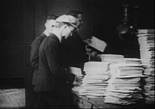 A black-and-white film still in the four corners. Three men in the center stand by a table on the right stacked with thousands of sheets of paper.