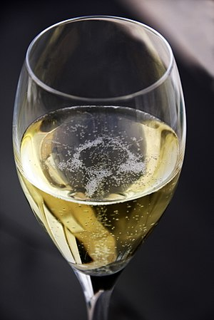 Champagne - A glass of Champagne exhibiting the characteristic bubbles associated with the wine