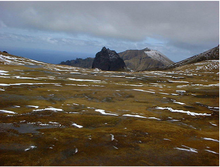 A bare strech of land with ice and snow patches, leading to rocky hills in the background