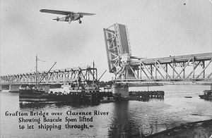 "Clarence River (New South Wales) - The Grafton Bridge over the Clarence River showing Bascule span lifted to let shipping through. (Postcard from about 1932; The ""Southern Cross"" aeroplane has been added to the photograph.)"