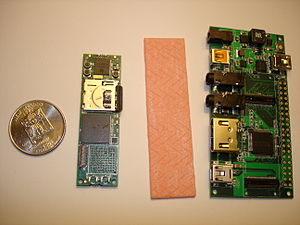 Gumstix - A side-by-side size comparison of a US Quarter, a Gumstix Overo Earth, a stick of gum, and the Gumstix Summit expansion board.