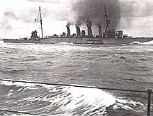 A large four-stacked warship billowing thick black smoke and moving through moderate seas