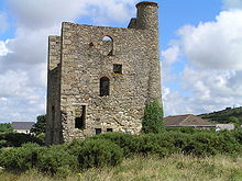 Ruined and overgrown stone building with a tall stone chimney