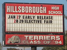 "Hillsborough High School letter board of upcoming events, with ""Terriers Class of '94"" and dog mascot logo."