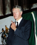 A white, grey-haired gentleman in a dark blue suit stands before a green and white flag with his left hand raised, as if he is coming to a main point in a speech.