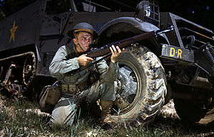 1942 in the United States - Infantryman wearing a Brodie helmet, kneeling in front of M3 Half-track, holds an M1 Garand rifle. Fort Knox, June 1942.