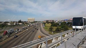 Interstate 880 - The Oakland Airport Connector traverses I-880 in Oakland, with Oakland–Alameda County Coliseum and Oracle Arena right of center.