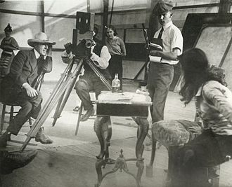 "D. W. Griffith - Left to right: Griffith, cameraman G. W. ""Billy"" Bitzer (behind Pathé camera), Dorothy Gish watching from behind Bitzer, Karl Brown keeping script, and Miriam Cooper in profile, in a production still for Intolerance (1916)."