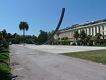 Vue d'une allée de parc dégagée avec palmier et sculpture contemporaine et une façade blanche imposante en fond.