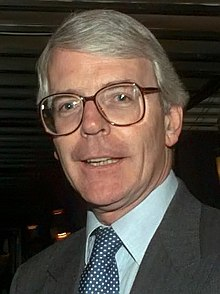 A portrait of a middle-aged man with grey hair, wearing large glasses and a dark suit