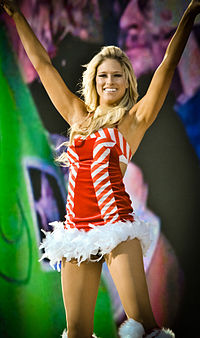 A blonde, Caucasian woman smiles while raising both her hands above her head. She is wearing a red and white dress with a white fur trim.