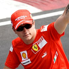 Kimi Räikkönen lifting his arm in the air while wearing a hat and sunglasses