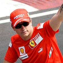 Kimi Räikkönen lyfter armen i luften med hatt och solglasögon
