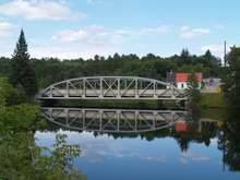 """A bridge crossing a river, the bridge reflects in the river. The steel girder bridge features an archway above the deck, with several beams interconnecting the arch with the deck."