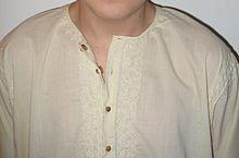 Kurta de cotton porté par un adolescent, patte boutonnée centrale, avec boutons amovibles en bois de santal, et broderies Chikan ton sur ton autour du col