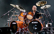 Short-haired man in a black shirt on a drum kit