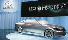"solid full-size car model on turntable, with ""Lexus Hybrid Drive"" listed behind."
