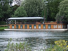 A colour image Gilmour's houseboat and studio the Astoria, anchored in a river. The background is green forest and it is a bright sunny day.