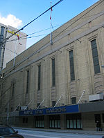 "An exterior view of a building. The building has a sign that says ""Maple Leaf Gardens"" on the front."