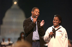 Marcus Allen - Marcus Allen with Yeoman 2nd Class Katherine Ward introduce Aretha Franklin during a concert in tribute to U.S. military members on the National Mall, September 4, 2003